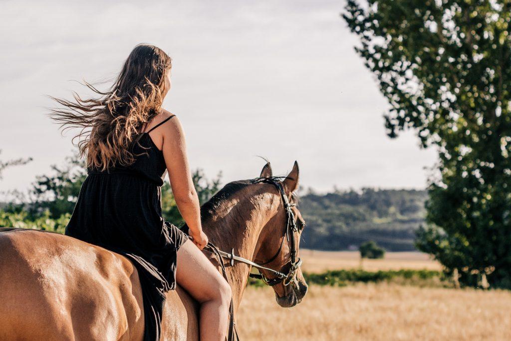 Junge Frau reitet das Pferd